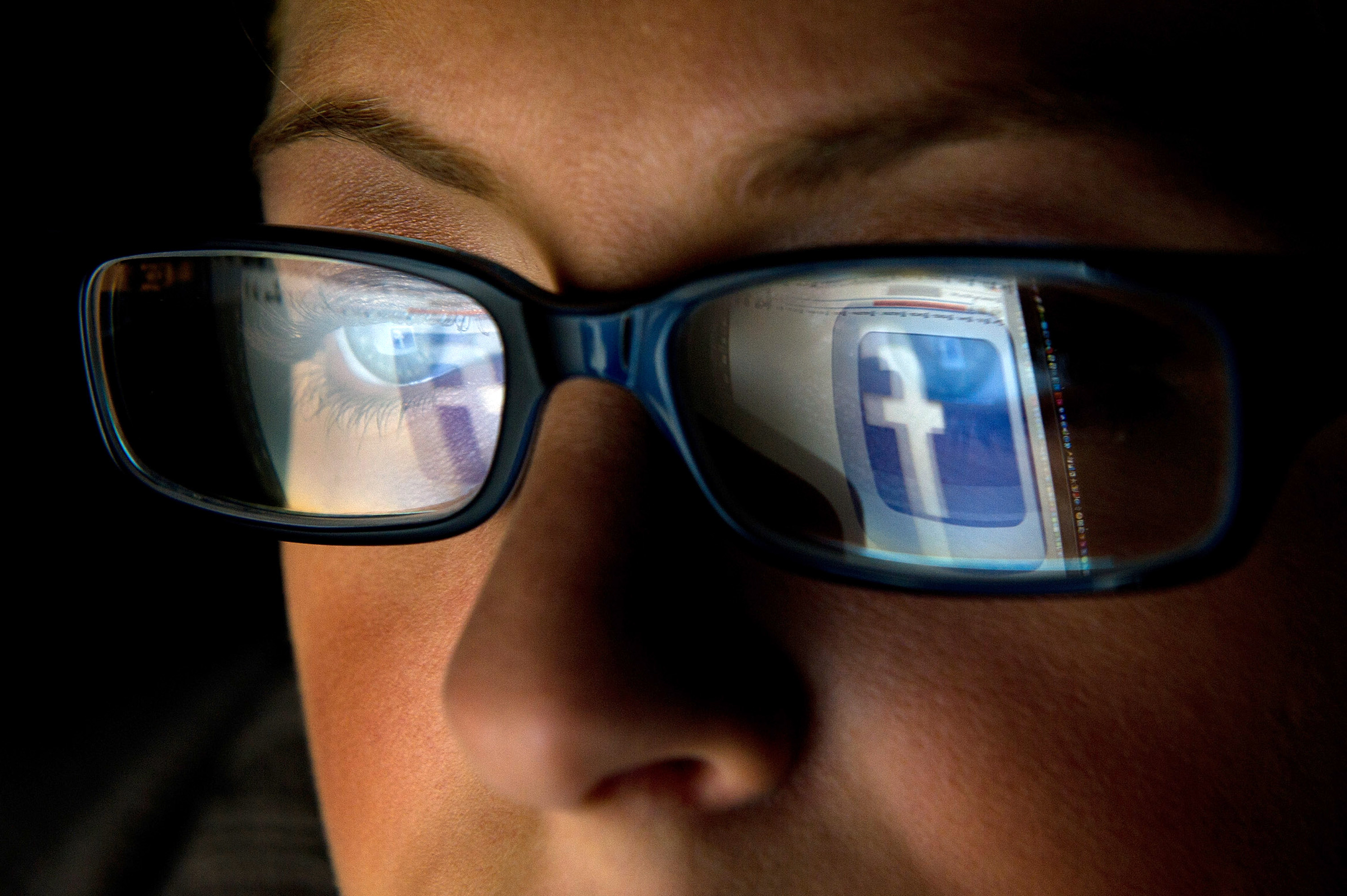 The Facebook logo is reflected in the eyeglasses of a user in San Francisco on Dec. 7, 2011.