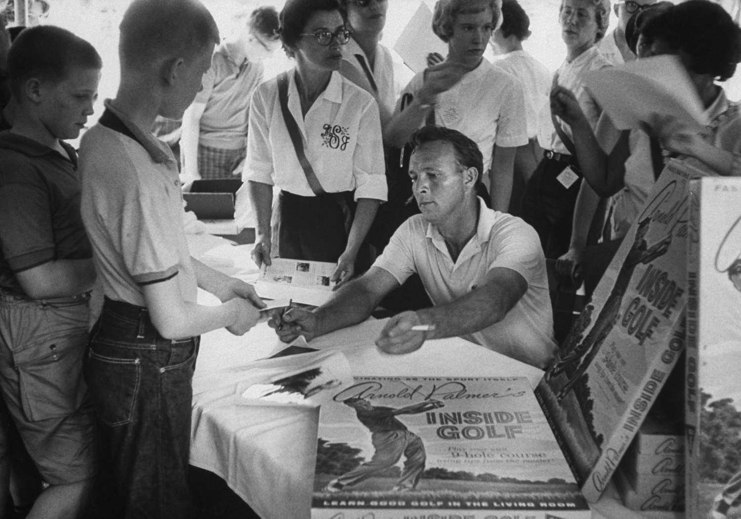 <b>Caption from LIFE.</b> Working a sideline which adds to biggest income in golf, Palmer signs autographs at stand filled with his products at a Wheeling, West Va., course.