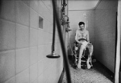 Quadriplegic Marke Dumpert, invalided out of the Marines as a lance corporal, waits helplessly to be dried in a veterans' hospital.