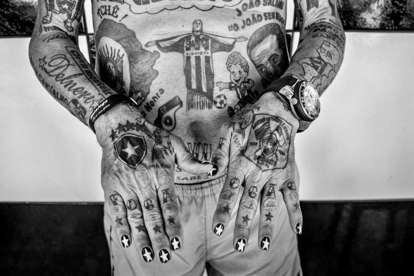 RIO DE JANEIRO, BRAZIL - JUNE 2014: Delneri Martins Viana, 69, has 82 tattoos that pay homage to his team, Botafogo. He has had the tattoos done over the course of 15 years, since he retired from the army. He goes to histattoo artist every Thursday to have a new tattoo done, or improve an old one. The tattoos include the team's shield, names of players, results of matches and even part of the club's anthem. He only owns clothes that have the Botafogo crest. Once a week he paints his finger and toe nails with the stars of theclub's logo. (Photo by Sebastián Liste/ Reportage by Getty Images)