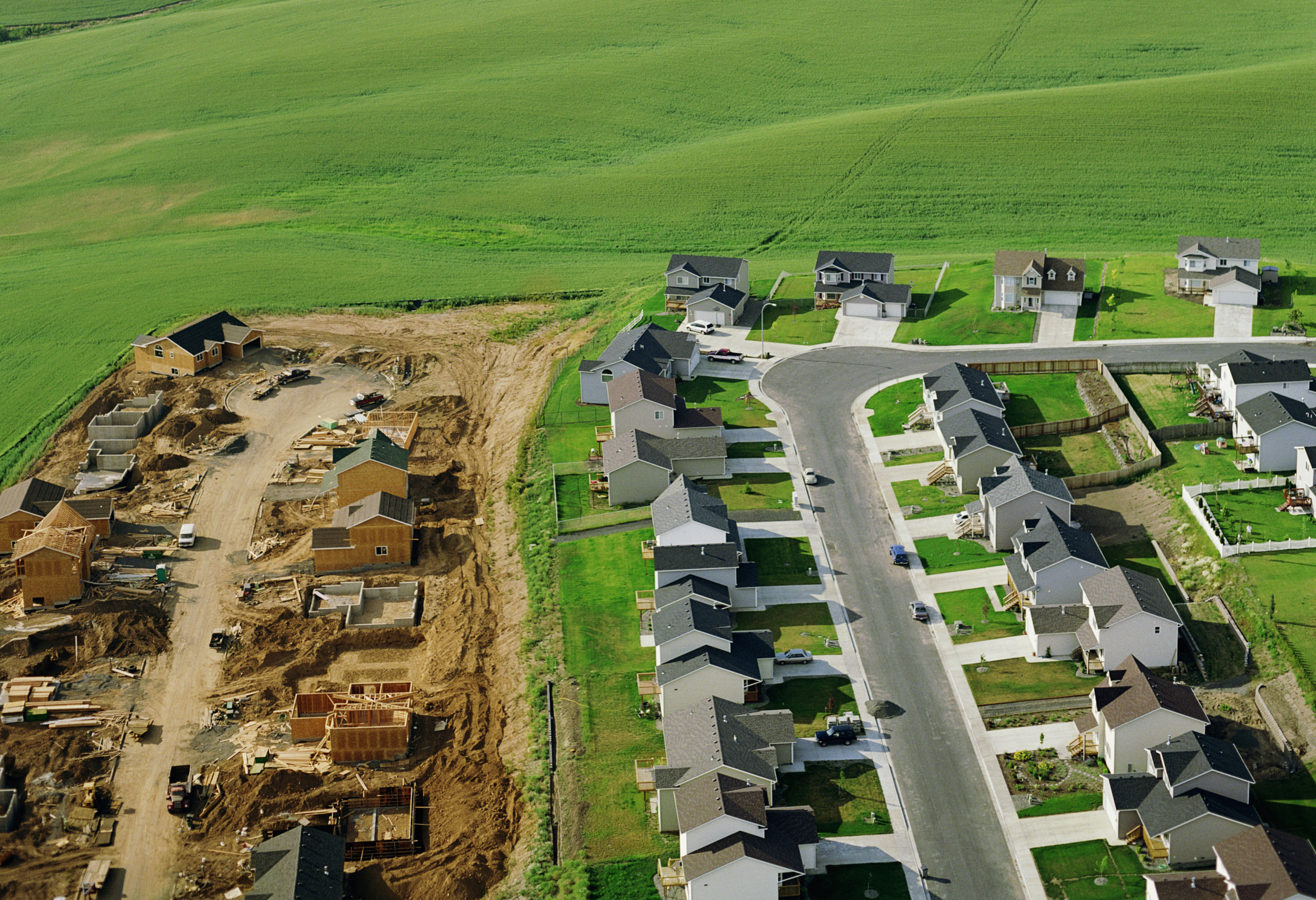 Housing development under construction on farmland, aerial view.