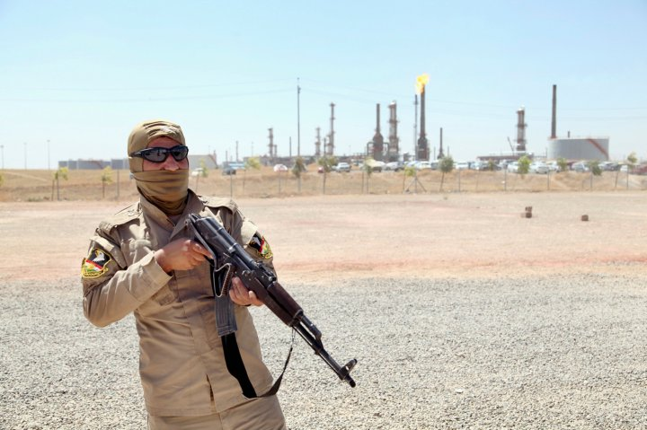 A member of Kurdish security forces takes up position with his weapon as he guards an oil refinery on the outskirts of Mosul
