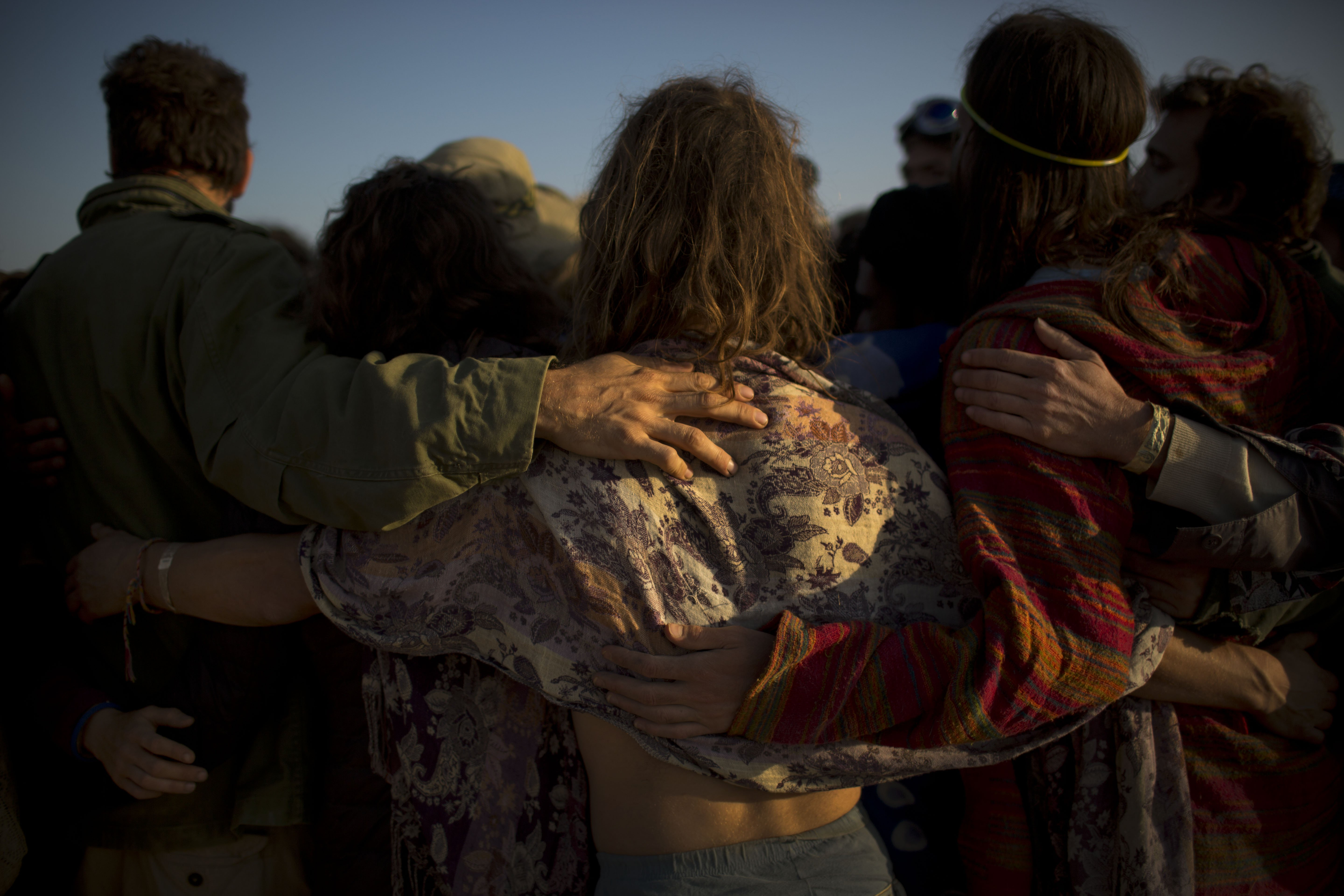 Israelis share a group hug after a wooden sculpture was set on fire at Israel''s first Midburn festival in the Negev Desert, Israel on June 7, 2014.