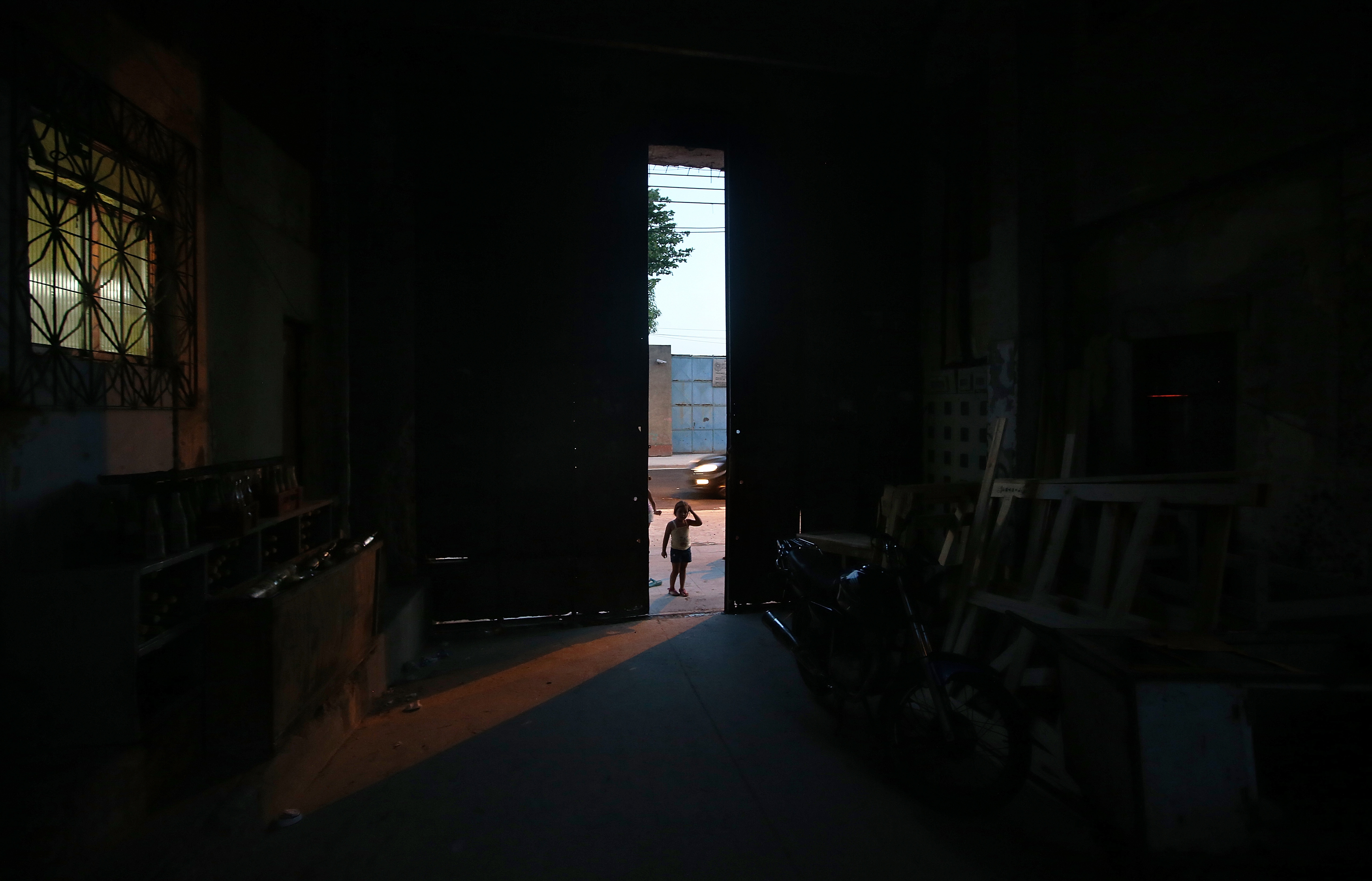 A girl stands outside the main entrance to a formerly deserted building which is currently home to 82 families who occupy the building in the port district on November 3, 2013 in Rio de Janeiro.