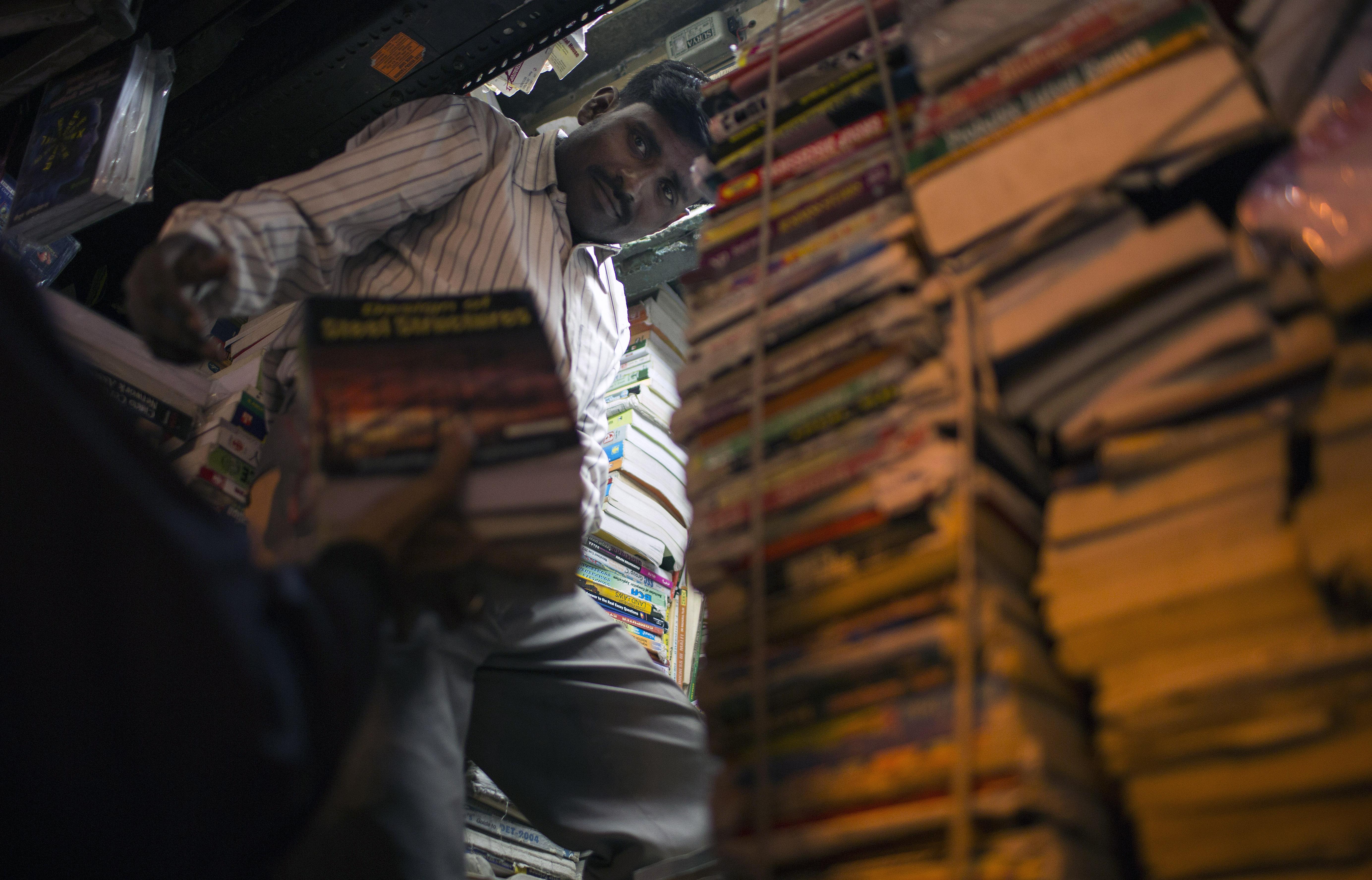 An Indian book vendor arranges items at his shop in New Delhi's Old Quarter on Jan. 30, 2013.