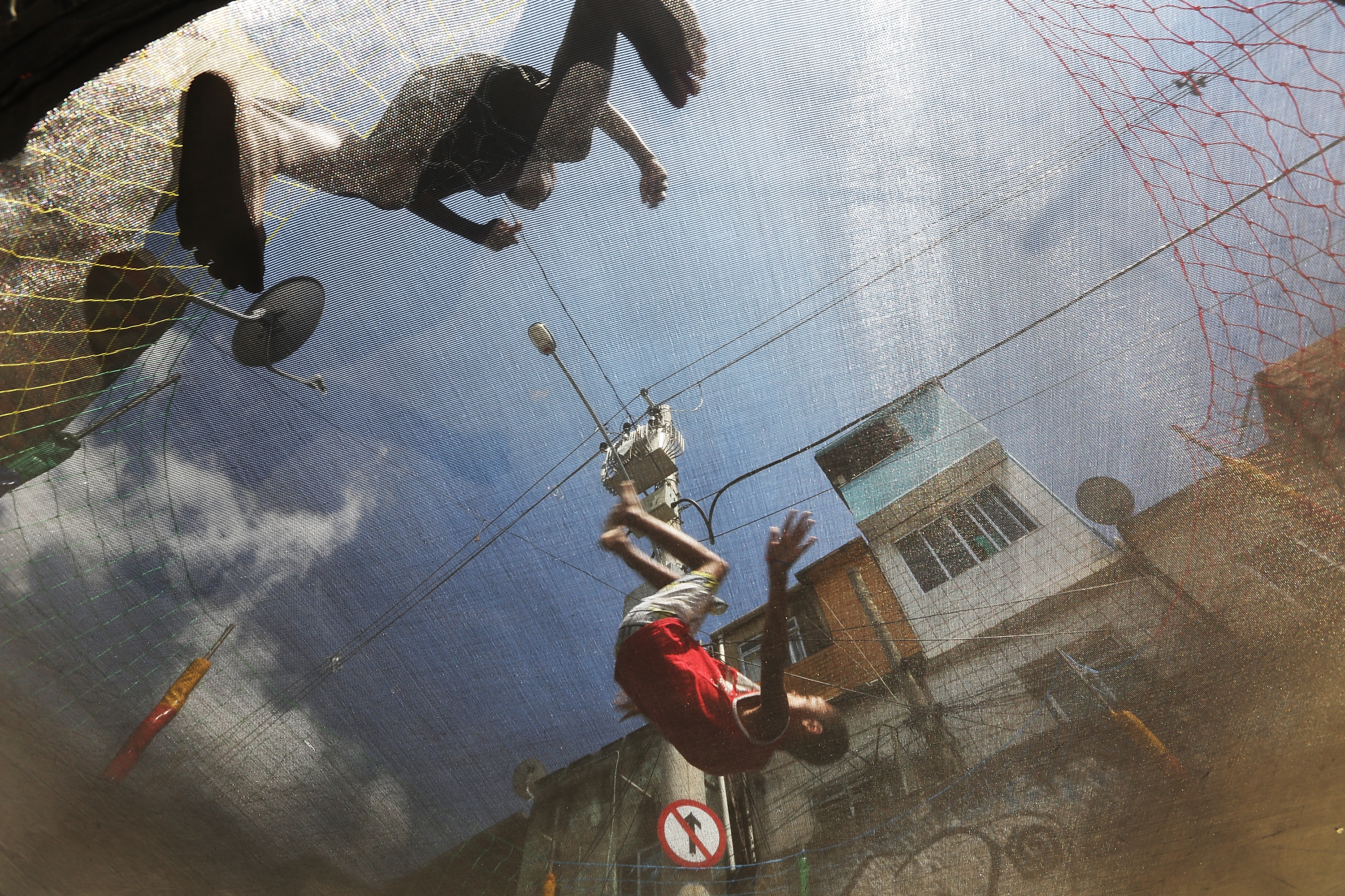 Boys play on a trampoline before the start of a communal marriage ceremony in the Mangueira pacified favela on November 9, 2013 in Rio de Janeiro.
