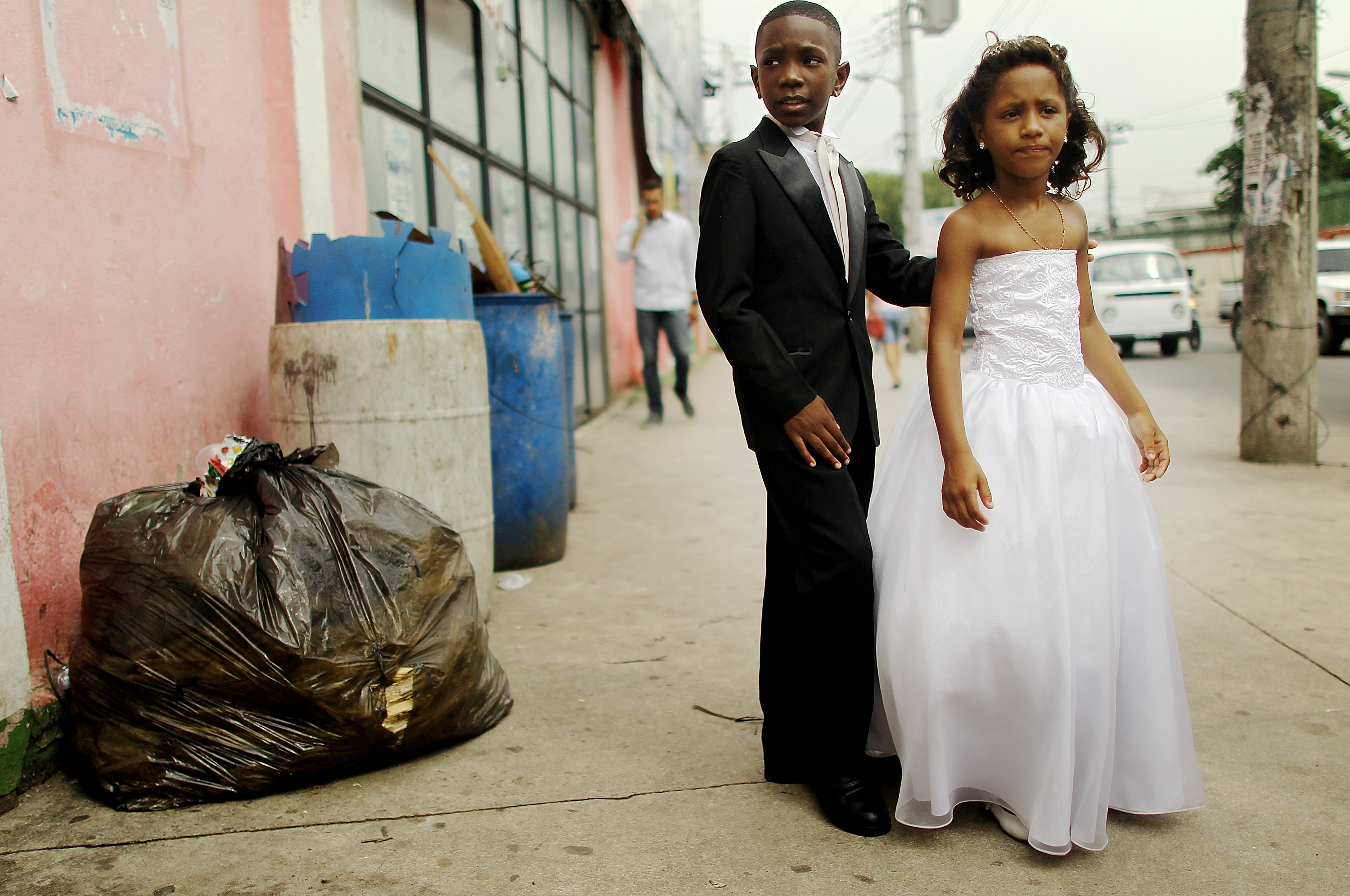 Young family members wait to enter a communal marriage ceremony in the Jacarezinho pacified favela, on January 17, 2014 in Rio de Janeiro.