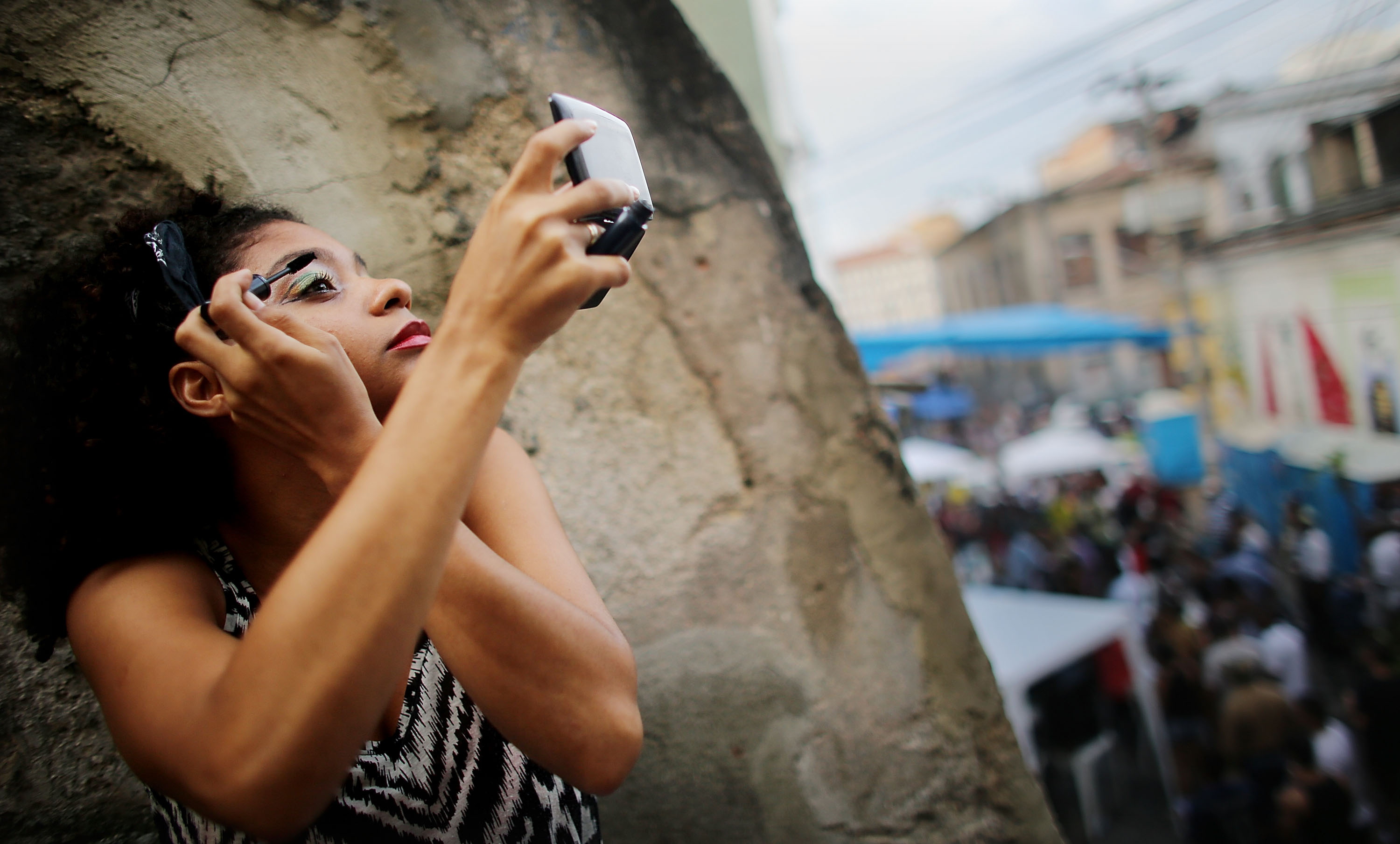 Performer Agatha Rosa with Grupo Orunmila applies her makeup before dancing at National Day of Samba celebrations at Pedra do Sal in the port district, on December 2, 2013 in Rio de Janeiro.