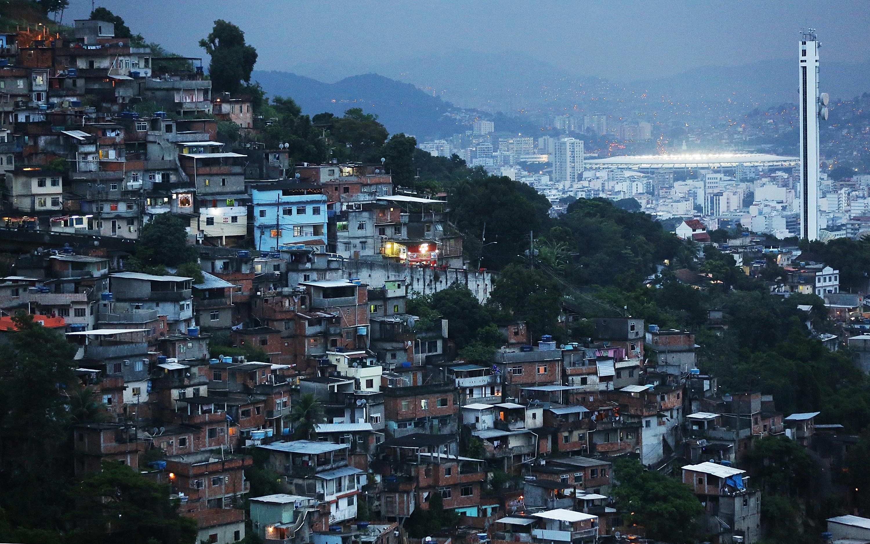 Rio's iconic Maracana Stadium is lit at dusk behind a favela on December 10, 2013 in Rio de Janeiro.