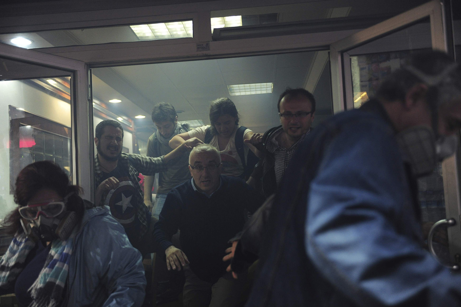 May 31, 2014. People try to escape from a cafe, after tear gas fired by riot police outside to disperse protesters seeped in, at central Istanbul , Turkey.
