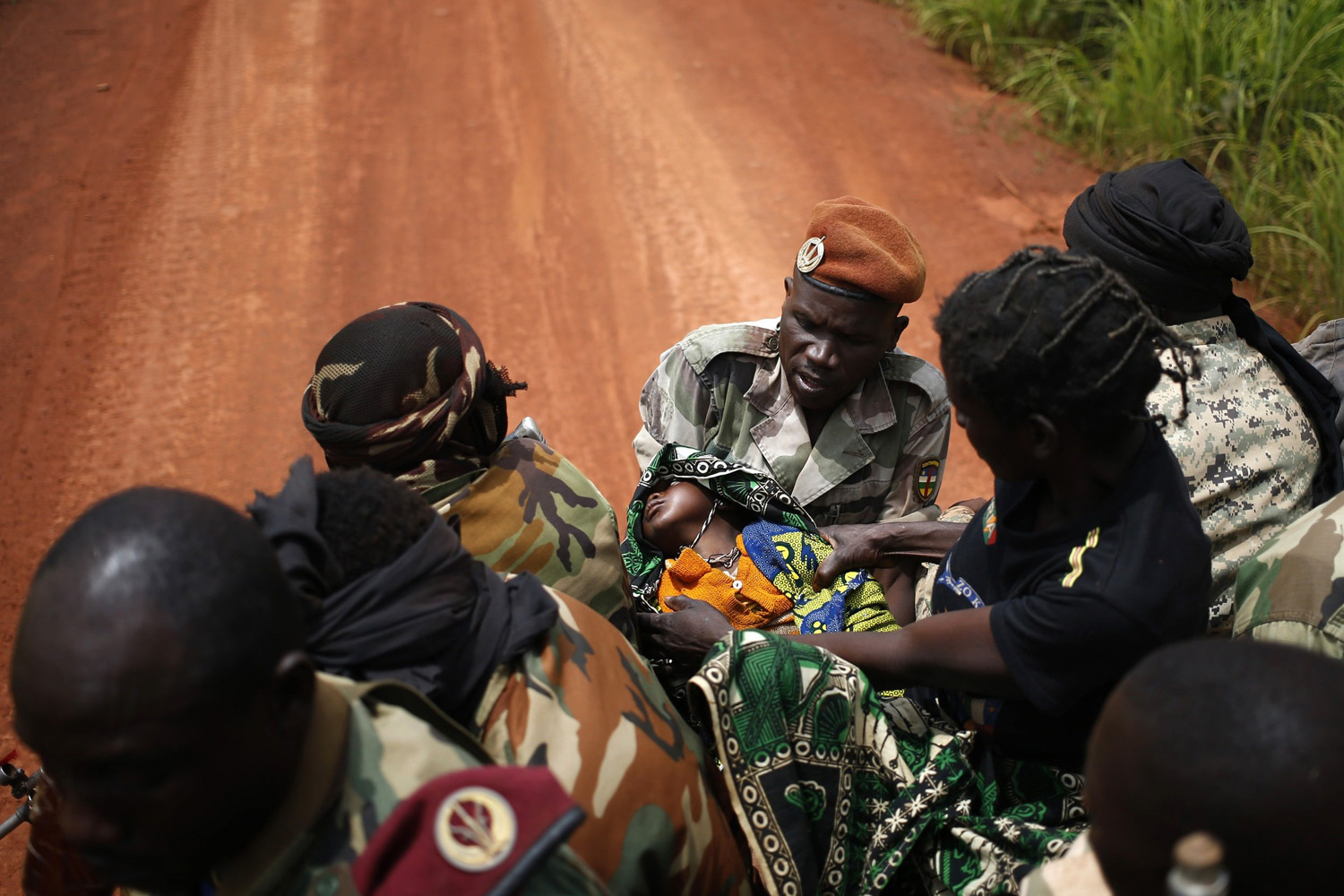 May 31, 2014. Seleka fighters carry a sick child to her mother, at a village between Bambari and Grimari.