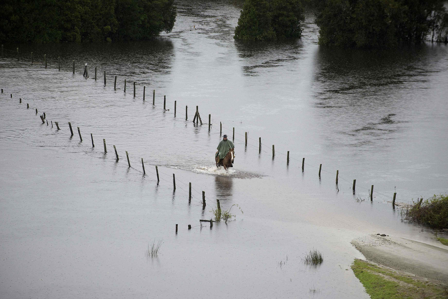 June 2, 2014. A resident rides his horse along a flooded road near Puerto Varas city, south of Santiago.