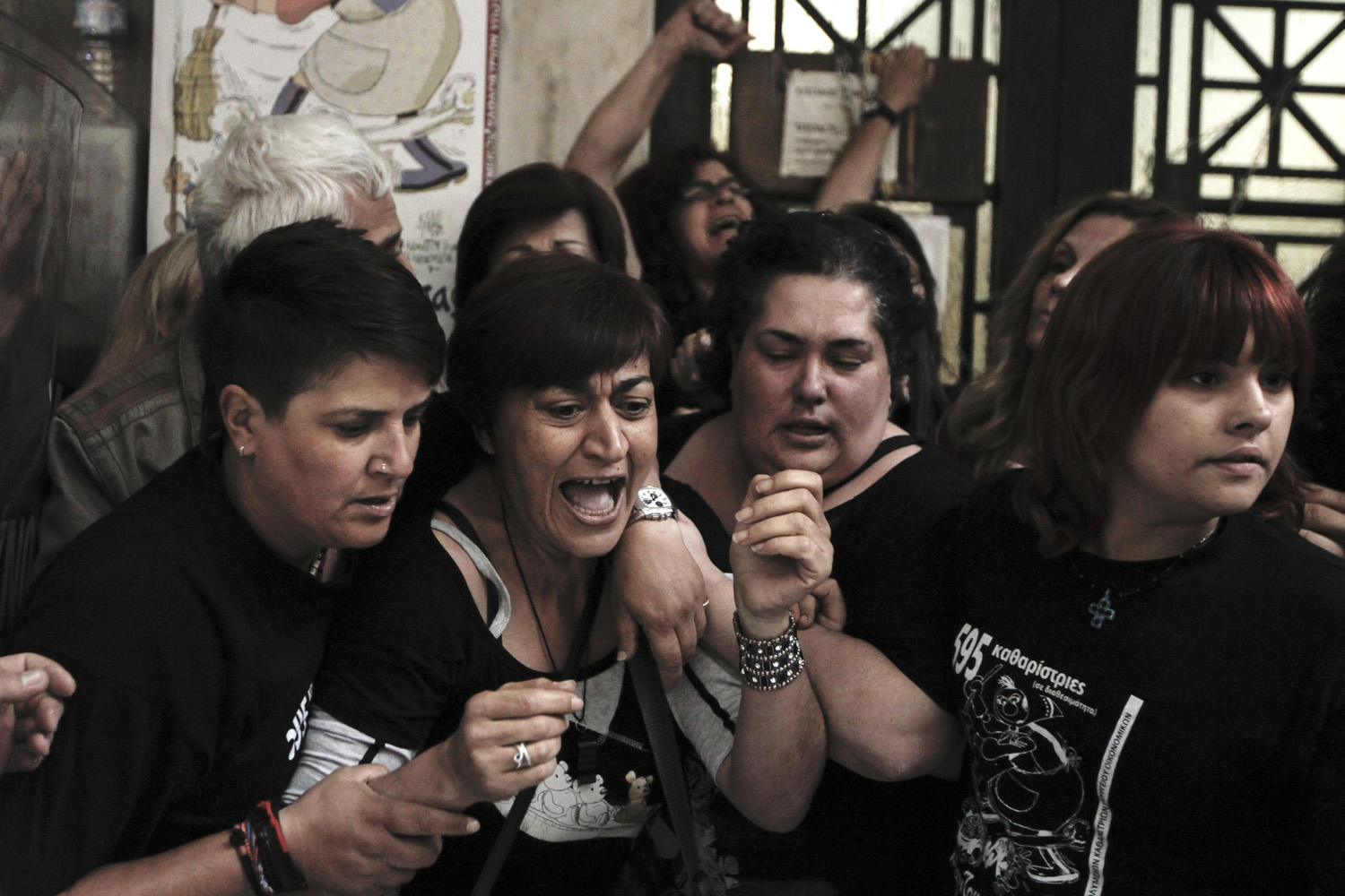 June 3, 2014. Cleaning ladies from the public sector react as they scuffle with police officers at the entrance of a building housing the Finance Ministry, during a protest against the layoffs and transitions due to a troika-led civil service revamp, in Athens.