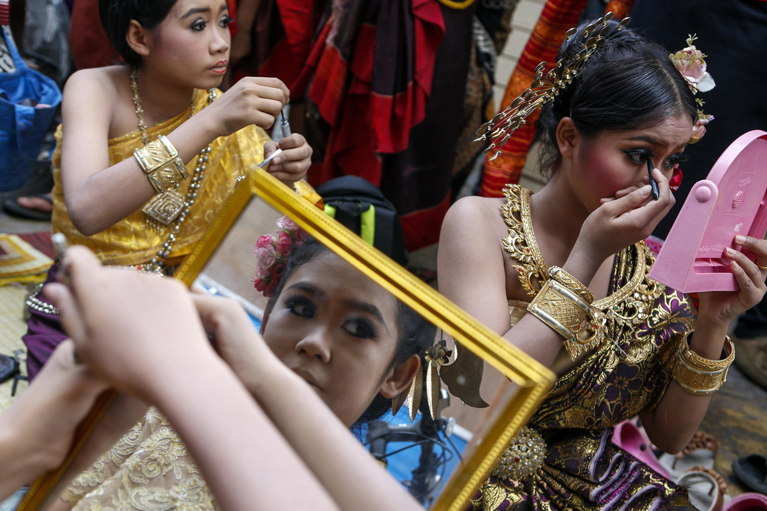 June 4, 2014. Dancers get their make up done backstage before their show at the Victory Monument during a military event in Bangkok.
