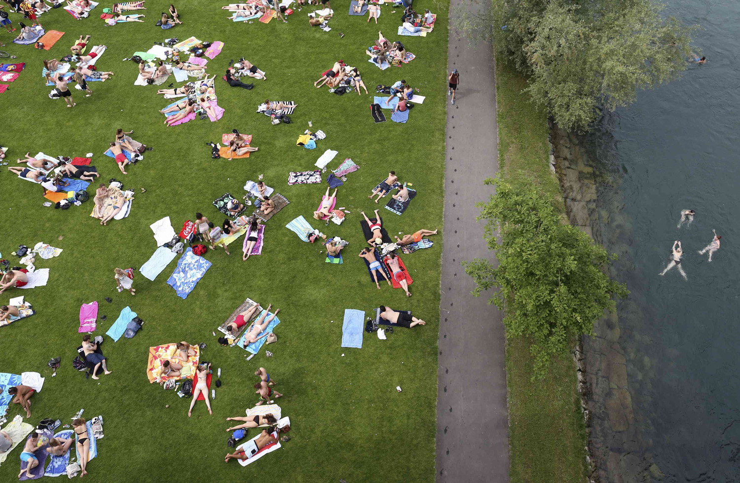 People sunbathe and swim in the river Aare on a hot summer day in Bern, Switzerland on June 7, 2014.