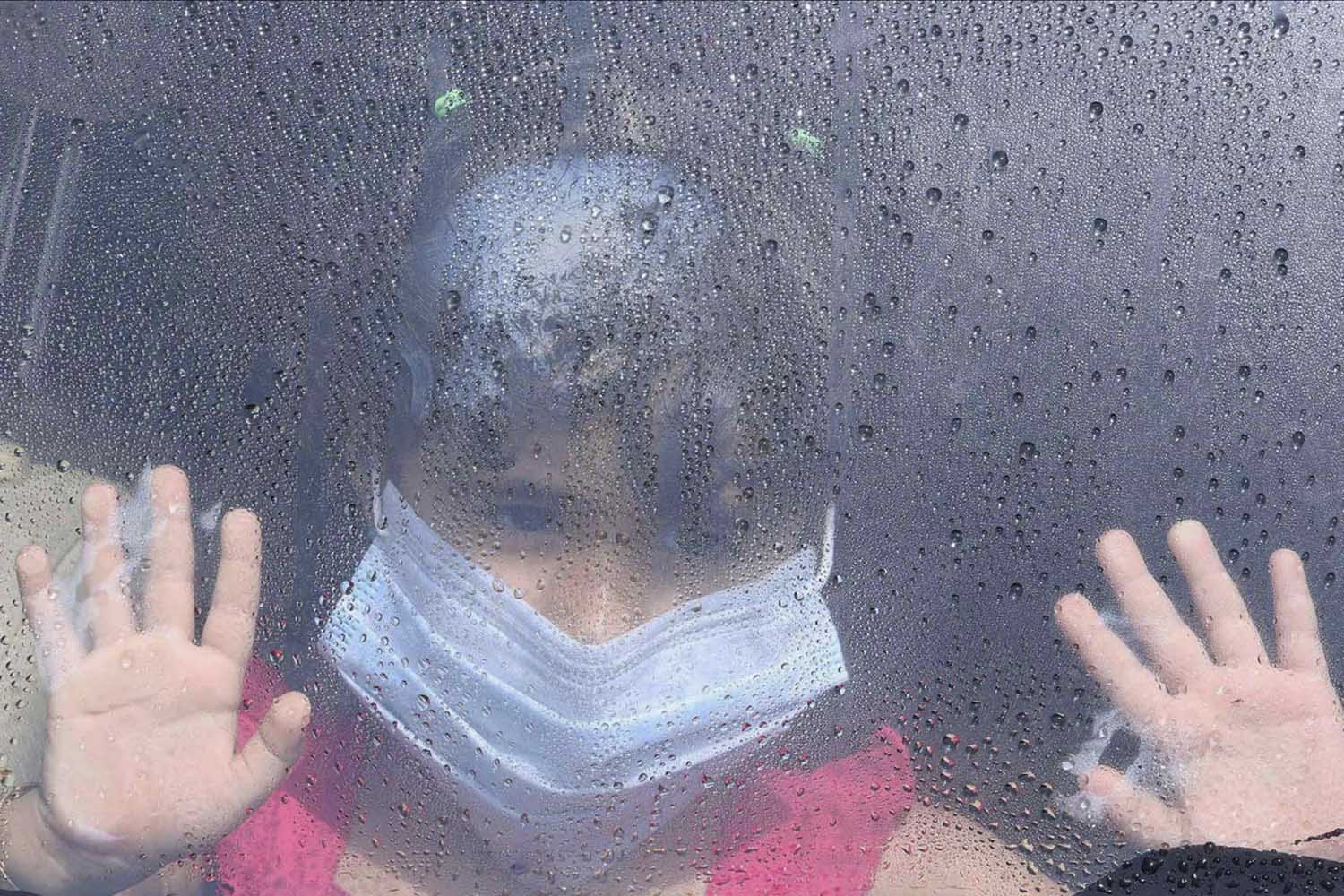 Jun. 7, 2014. A girl wearing a mask looks out a car window as rain drops are seen in Taif.  A dramatic upward revision in the number of people killed by the MERS virus in Saudi Arabia may signal a fresh approach from Riyadh, but also raises new questions about how the two-year-old outbreak has been handled.