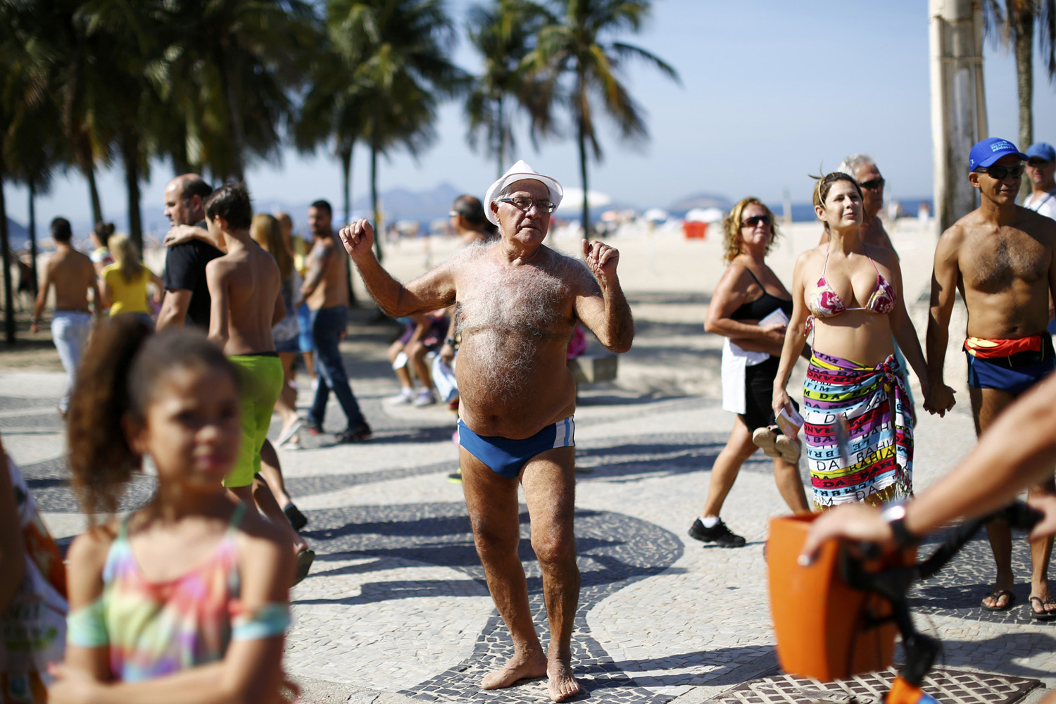A man dances during a parade with puppets depicting soccer players at Copabana beach in Rio de Janeiro, June 8, 2014.