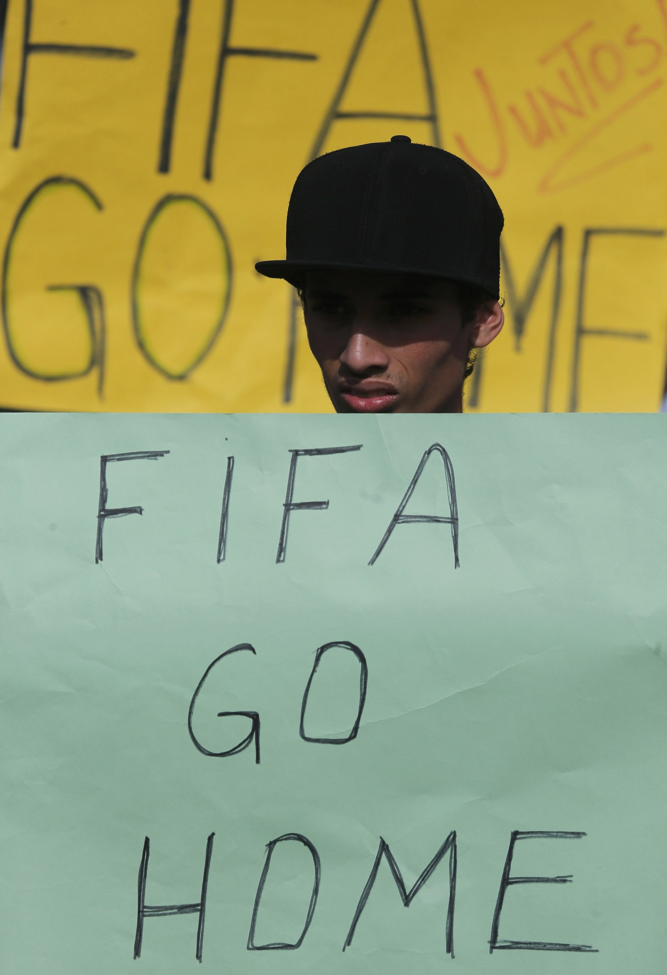 An activist holds a protest poster in front of the municipal stadium prior to a training session by Japan's national soccer in the town of Sorocaba, June 8, 2014.