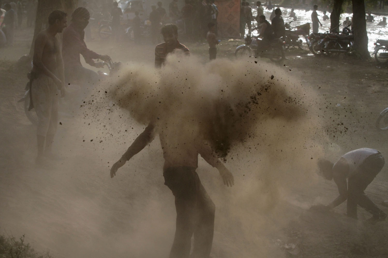 Jun. 8, 2014. Locals play with dirt before a dip to cool off in a nearby canal on a hot day in Lahore.