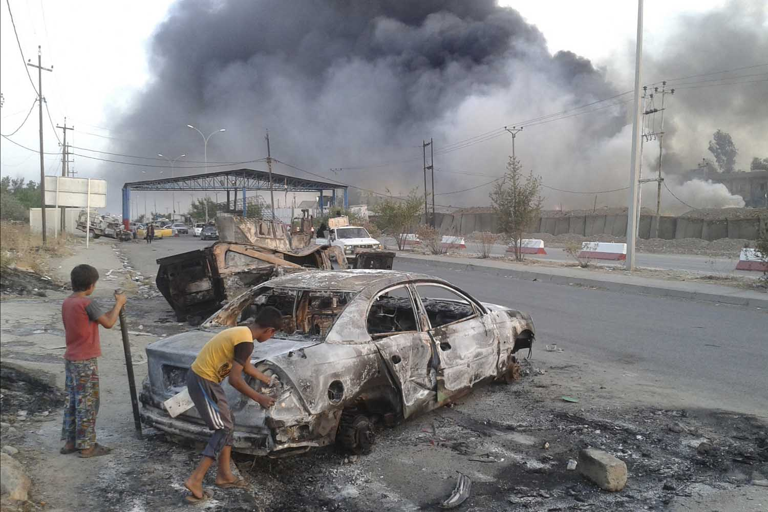 Jun. 10, 2014. Civilian children stand next to a burnt vehicle during clashes between Iraqi security forces and al Qaeda-linked Islamic State in Iraq and the Levant (ISIL) in the northern Iraq city of Mosul.