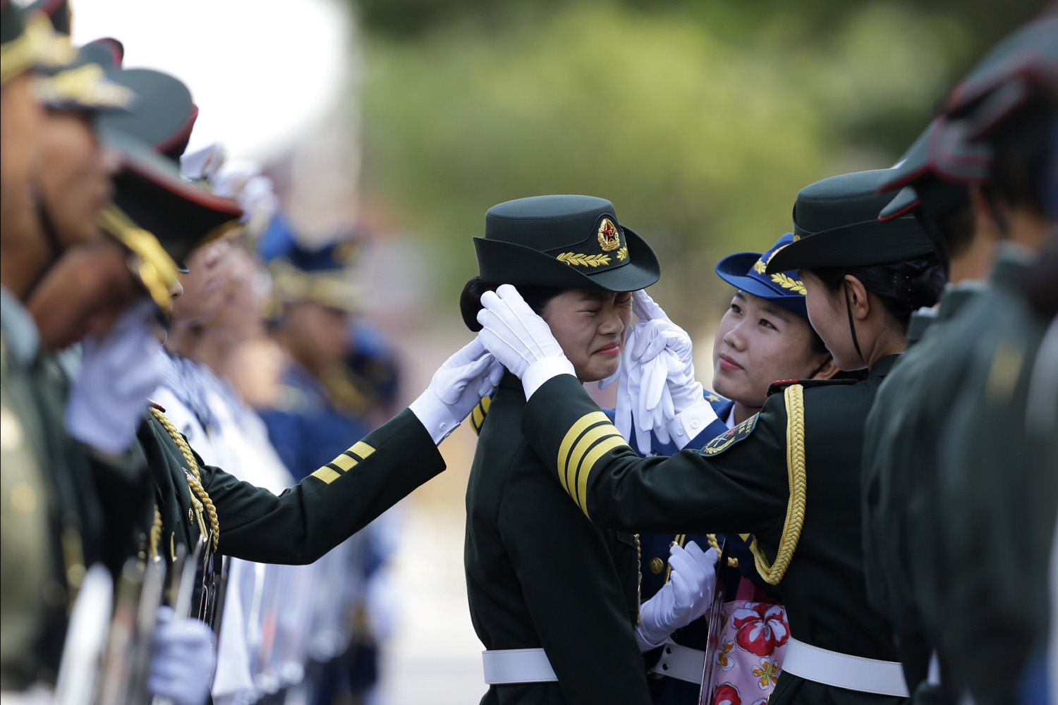 Jun. 11, 2014. A female member of the honor guard reacts as another one helps to adjust her cap ahead of an official welcoming ceremony for Italy's Prime Minister Matteo Renzi outside the Great Hall of the People in Beijing.