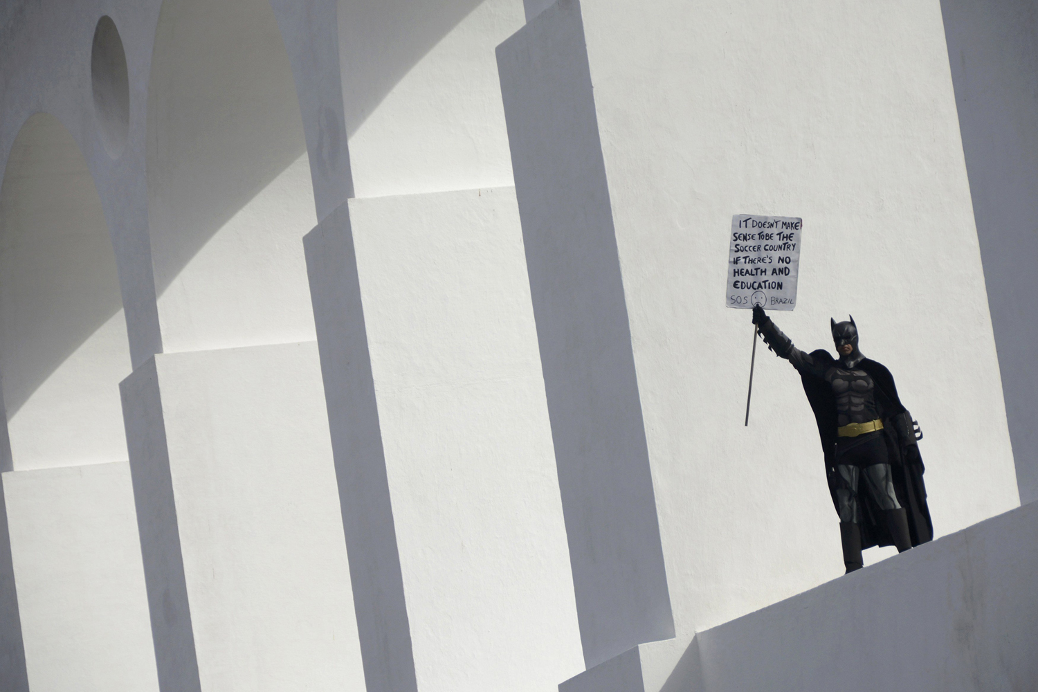Jun. 12, 2014. An anti-government demonstrator dressed as Batman holds a sign on the Lapa Arches during a protest against the 2014 World Cup in Rio de Janeiro.
