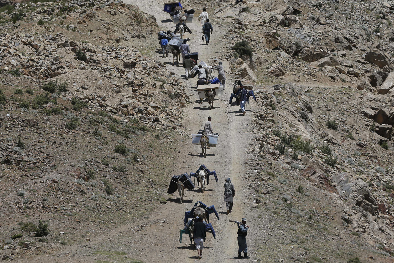 Jun. 13, 2014. Afghan men lead donkeys loaded with ballot boxes and other election material to be transported to polling stations which are not accessible by road in Shutul, Panjshir province.