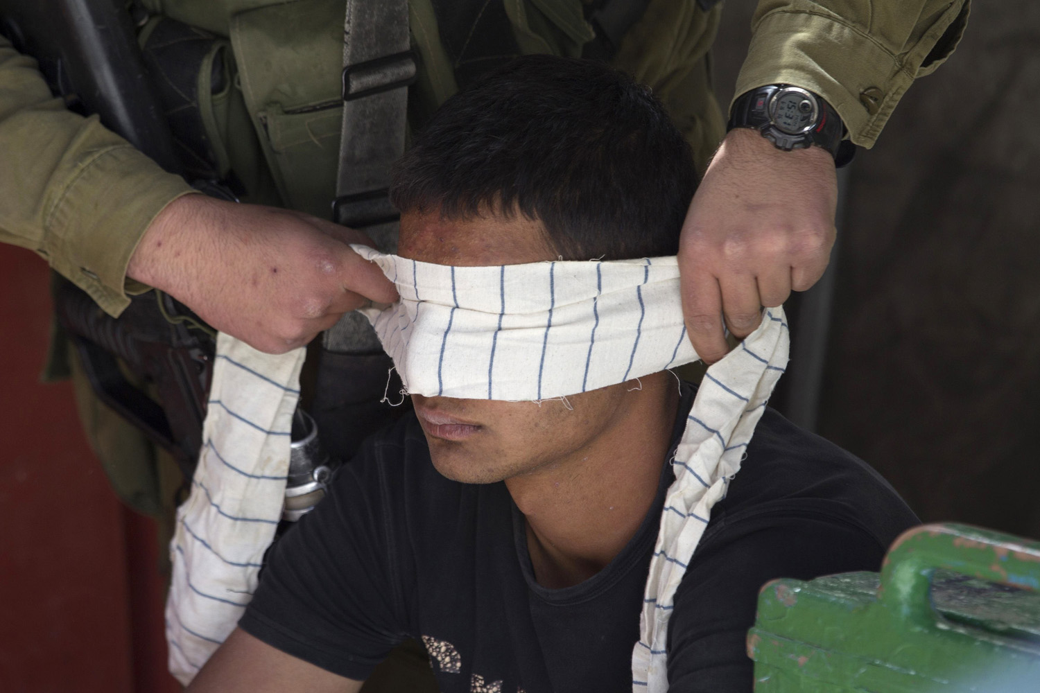 Jun. 16, 2014. An Israeli soldier blindfolds of a Palestinian suspected of throwing stones as he detains him during clashes in the West Bank City of Hebron.