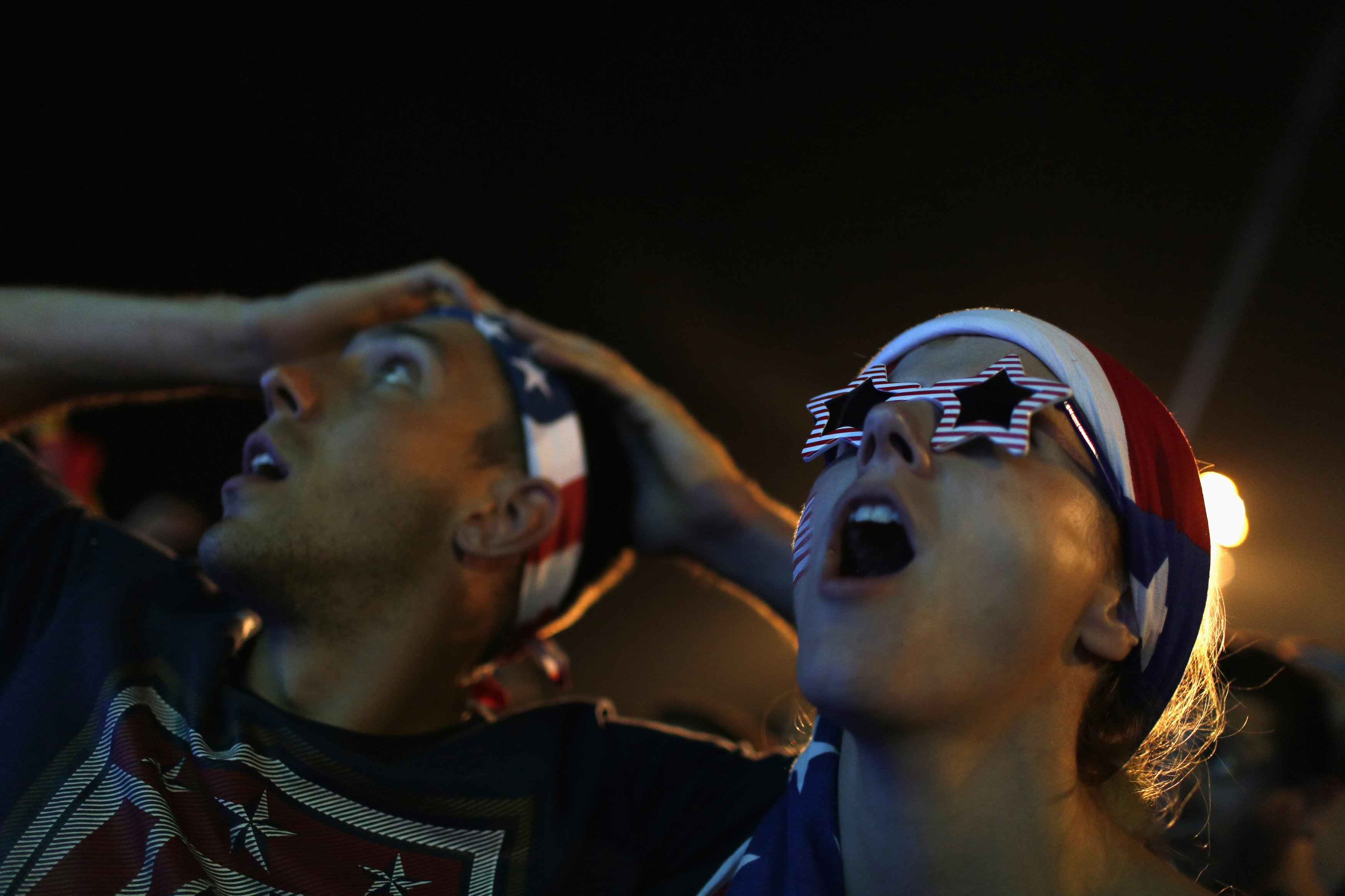 U.S. soccer fans react  as they watch the 2014 World Cup soccer match between U.S. and Ghana, which is broadcast on a large screen at Copacabana beach, in Rio de Janeiro on June 16, 2014.