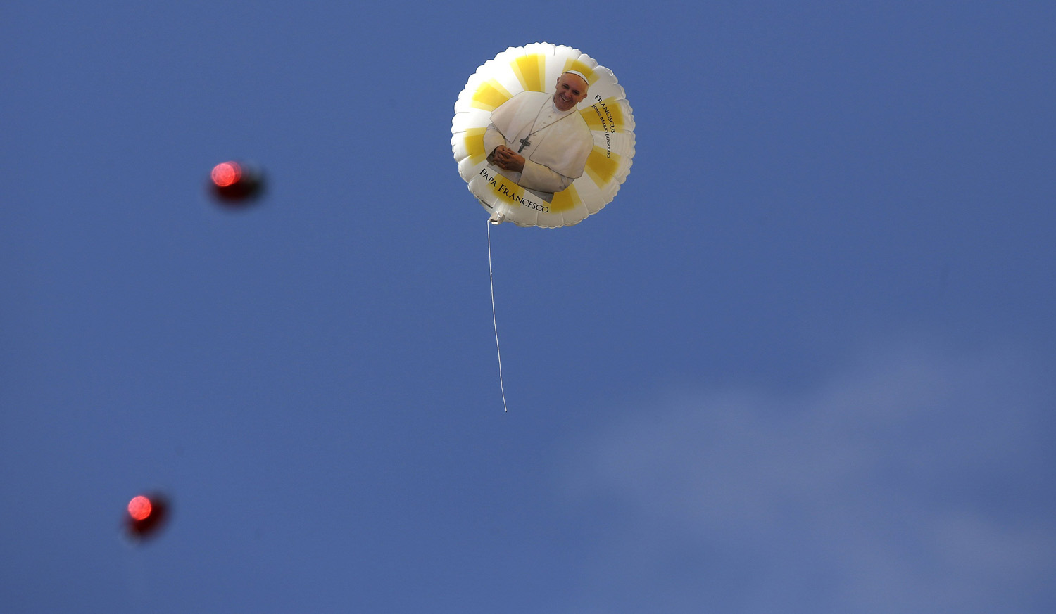 A balloon with an image of Pope Francis flies through the air at St. Peter's Square at the Vatican on June 18, 2014.