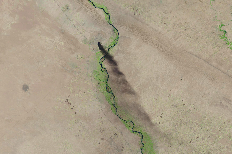 Jun. 18, 2014. A U.S. Geological Survey satellite image shows smoke rising from the Baiji refinery near Tikrit, Iraq.