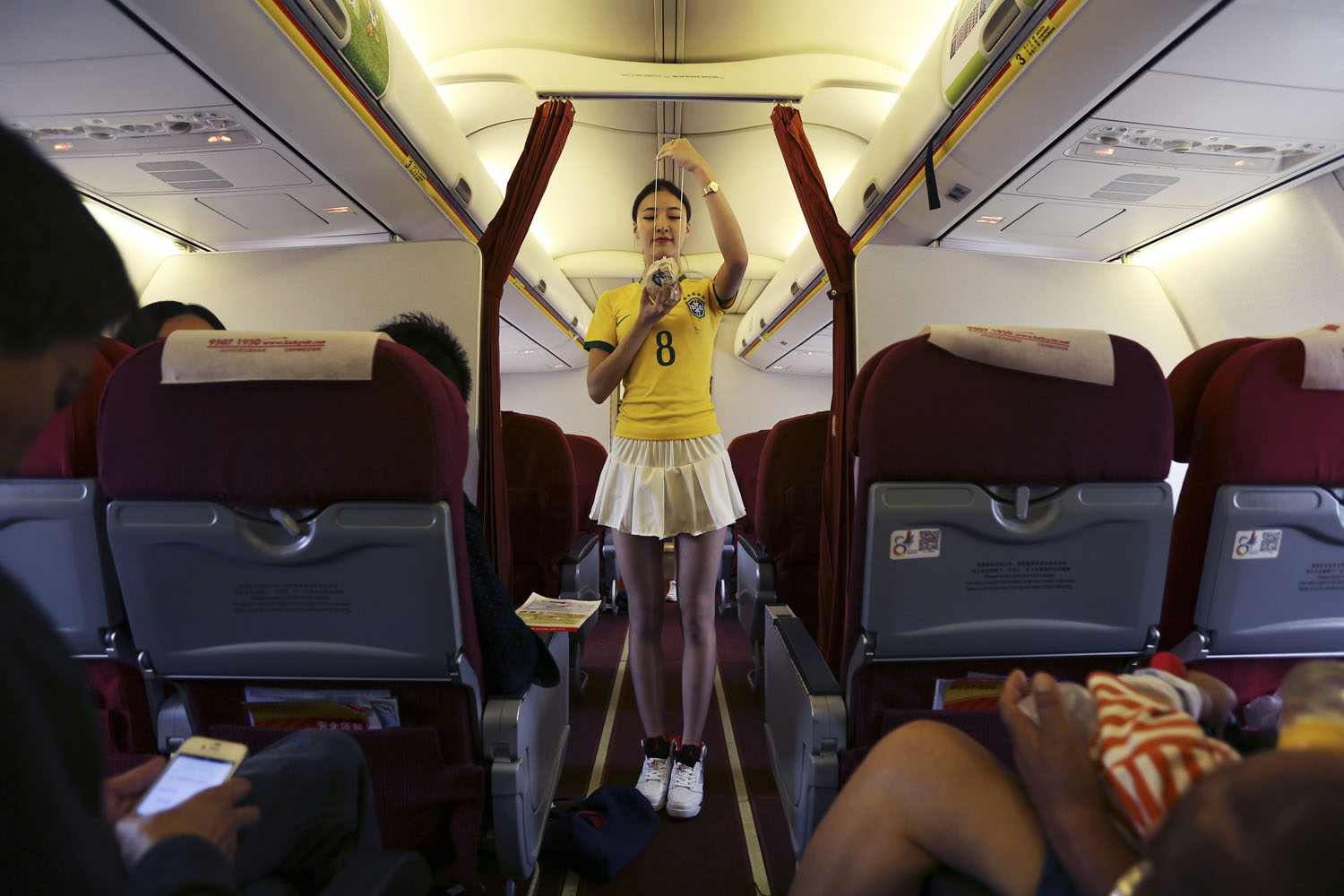 Jun.23, 2014. A flight attendant wearing a Brazil soccer team jersey demonstrates the emergency mask on an airplane traveling from Kunming to Hangzhou.