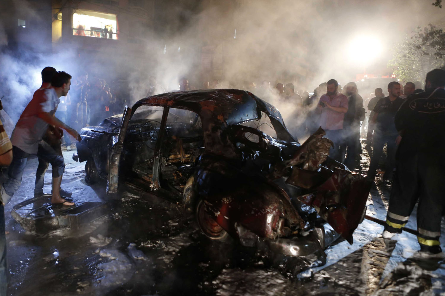 Jun. 23, 2014. People gather at the site of an explosion at the southern suburbs of the Lebanese capital Beirut. An explosion shook the southern suburbs of the Lebanese capital Beirut on Monday night, residents said.