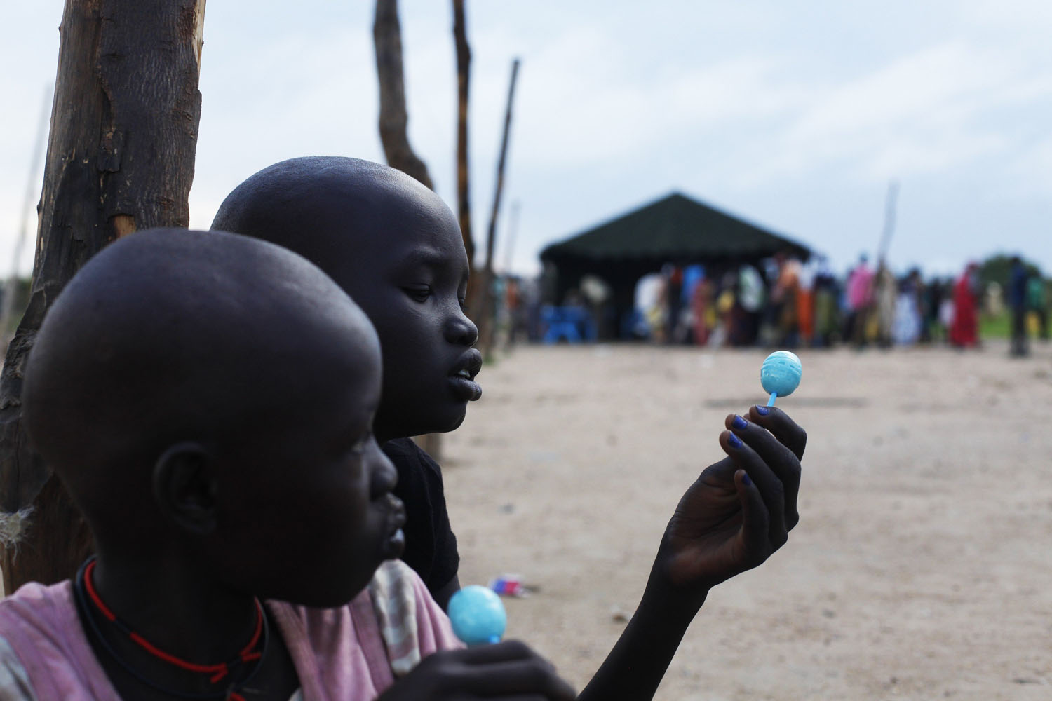 Jun. 26, 2014. Two girls are eating sweets as they wait for food during food distribution in Minkaman, Lakes State. About 94,000 people have sought refuge in Minkaman after fighting broke out in neighboring states, according to the International Organization for Migration.