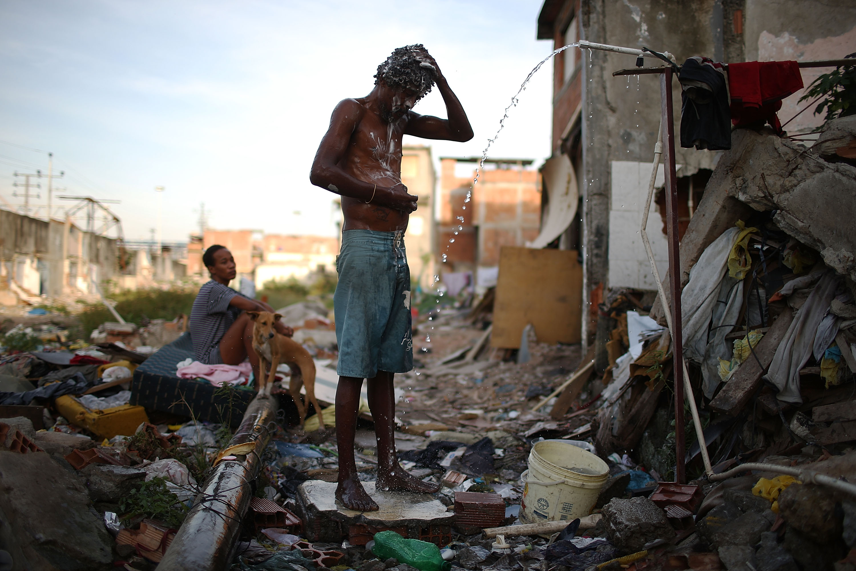 A man bathes from a small hose amongst the remains of demolished homes in the Metro Mangueira favela, located near Maracana stadium, on May 22, 2014 in Rio de Janeiro.