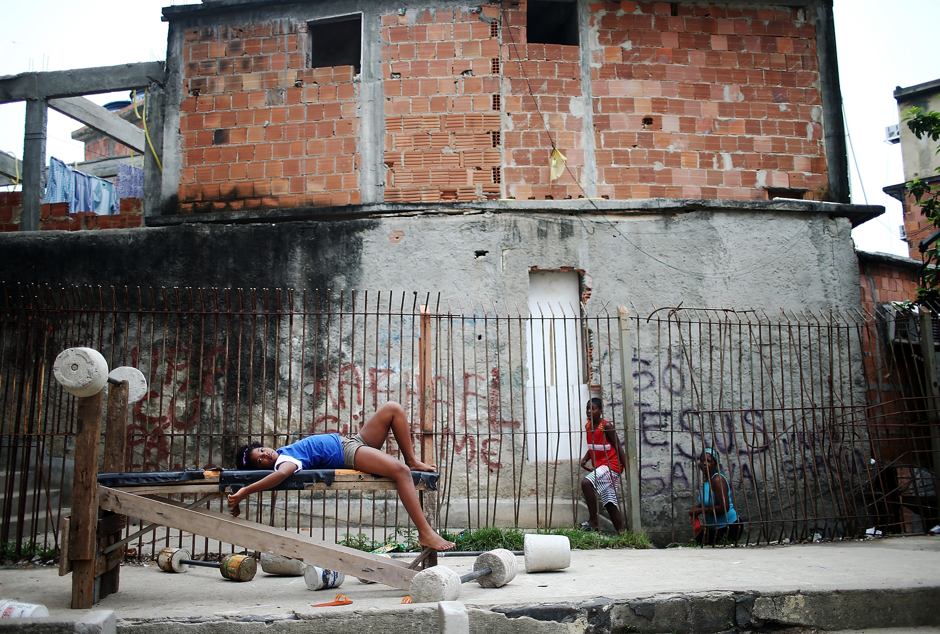 People gather by a makeshift weight set outside the Capela Nossa Senhora de Fatima which held Easter Mass during Semana Santa (Holy Week) in the Cantagalo shanty town community on April 20, 2014 in Rio de Janeiro.