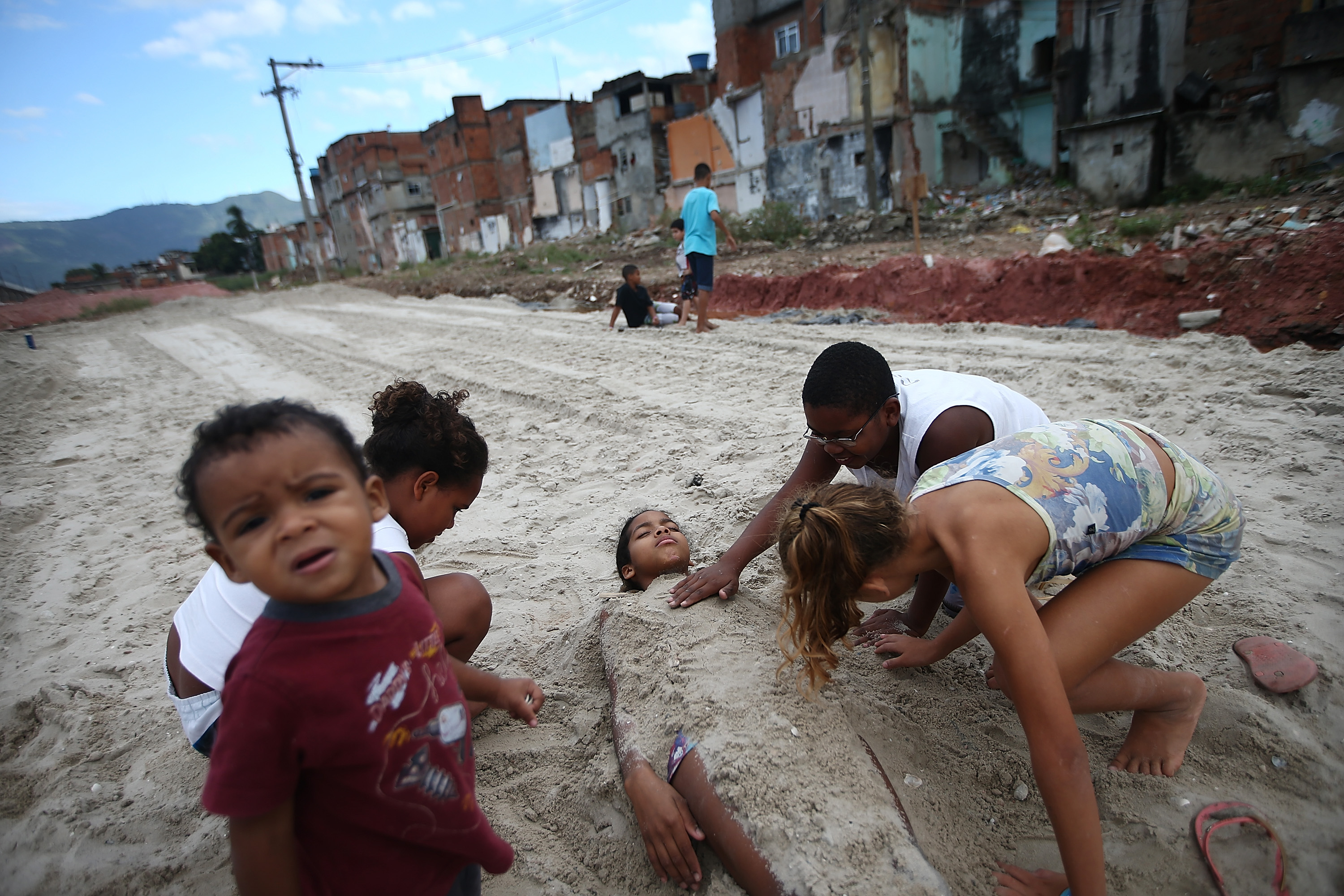Kids play in dirt from construction in an area where homes were torn down in the Manguinhos community on May 27, 2014 in Rio de Janeiro.