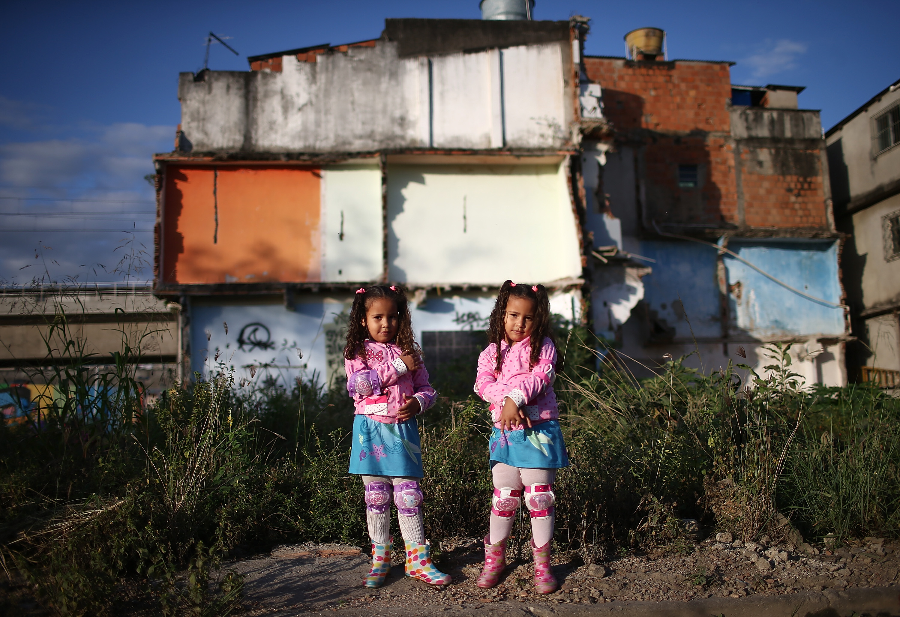 Twins Wendy (R) and Isis Guimaraes (L) pose in front of their home which remains standing in an area where homes were torn down in the Manguinhos community on May 27, 2014 in Rio de Janeiro.
