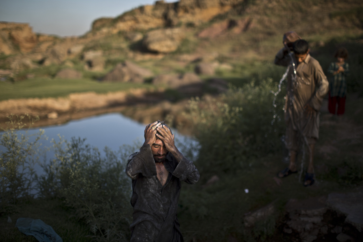 June 4, 2014.  A Pakistani daily laborer, applies soap on his body, while he and a youth bathe at a well, on the outskirts of Islamabad. Pakistanis are facing a shortage of clean drinking water due to the low level of water in the country's dams.