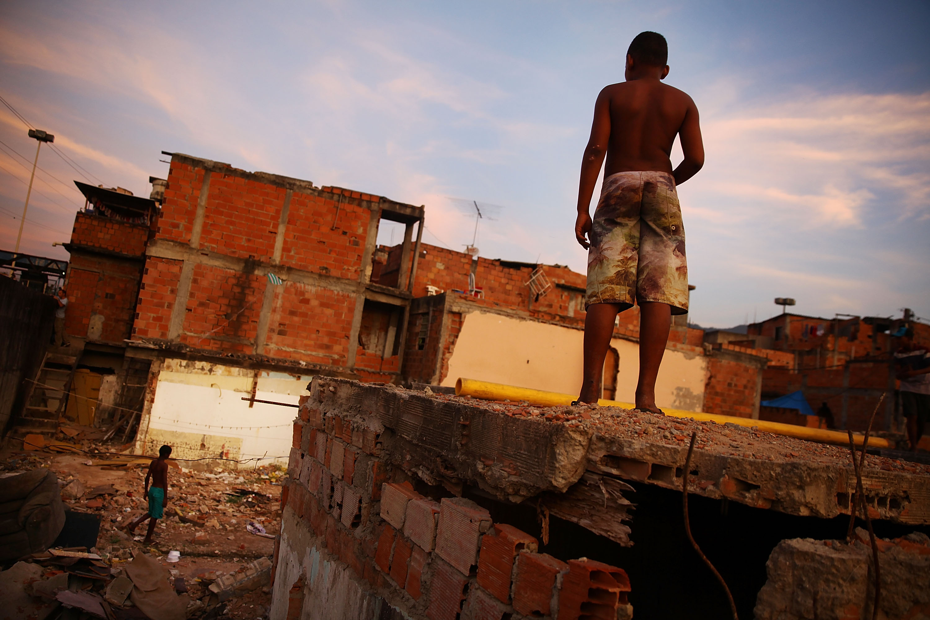 A boy stands on a roof near the remains of demolished homes in the Metro Mangueira favela, located near Maracana stadium, on May 22, 2014 in Rio de Janeiro.