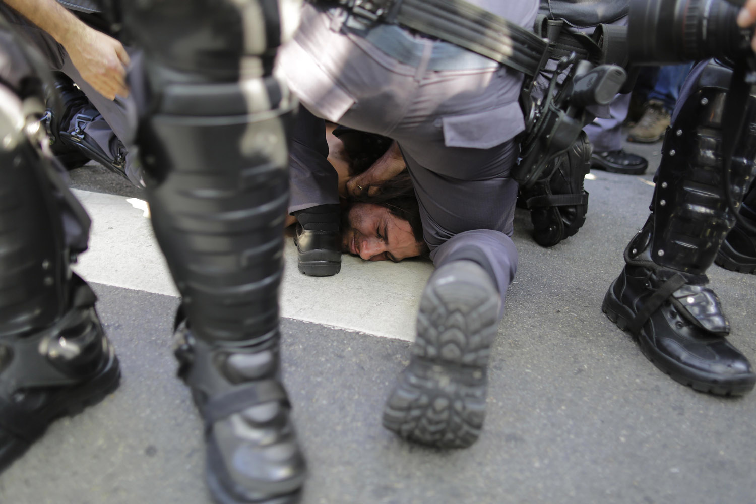 Jun. 12, 2014. A protester is detained by police during a demonstration demanding better public services and protesting the money spent on the World Cup soccer tournament in Sao Paulo, Brazil.