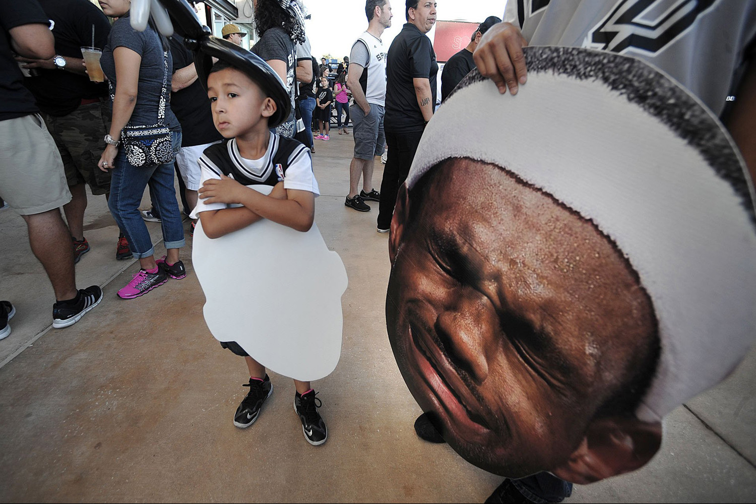 June 5, 2014. A young San Antonio Spurs fan stands next to a giant LeBron James face before the Spurs play host to James and the Miami Heat in Game 1 of the NBA Finals, at the AT&T Center in San Antonio.