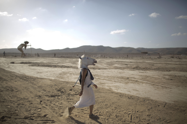 An Israeli woman wears a unicorn mask as she walks on the playa at Israel''s first Midburn festival in the Negev Desert, Israel on June 6, 2014.
