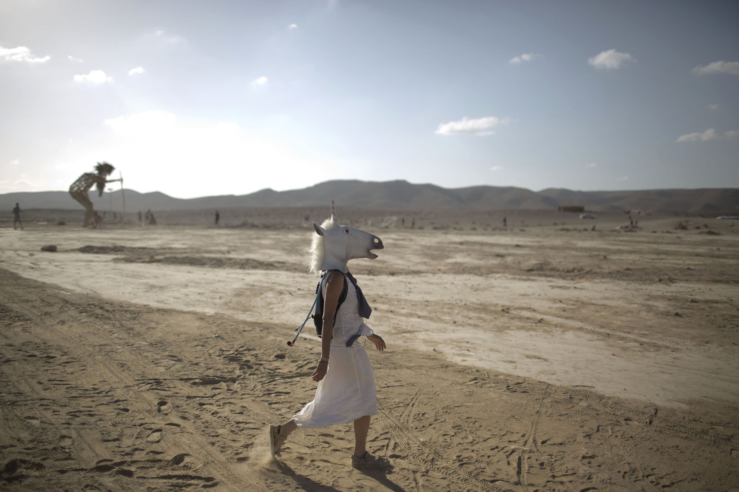 June 6, 2014. An Israeli woman wears a unicorn mask as she walks in the playa during Israelís first Midburn festival, modeled after the popular Burning Man festival, in the desert near the Israeli kibbutz of Sde Boker.