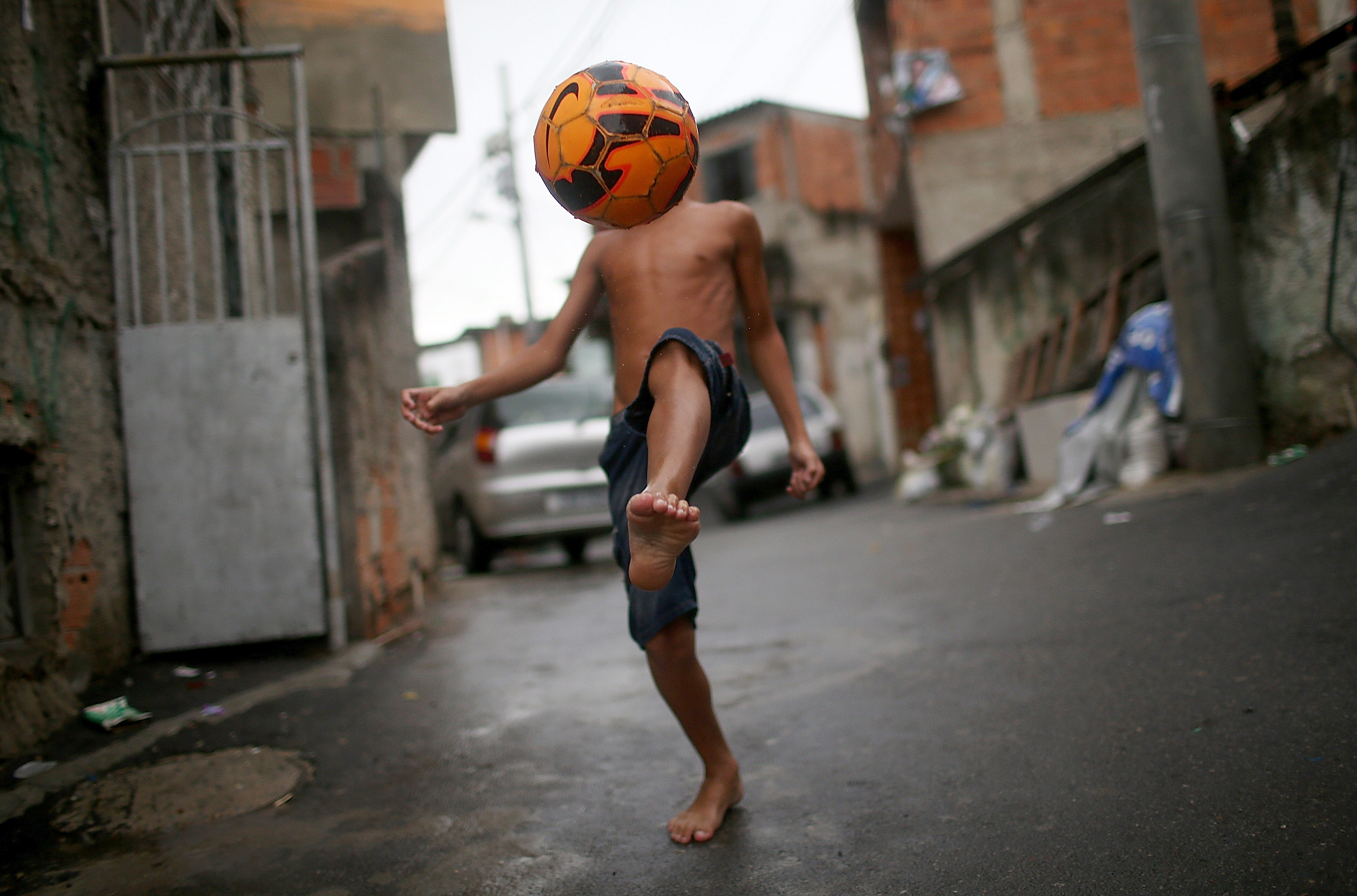A boy shows off his soccer skills in the Complexo do Alemao pacified favela on March 23, 2014 in Rio de Janeiro.