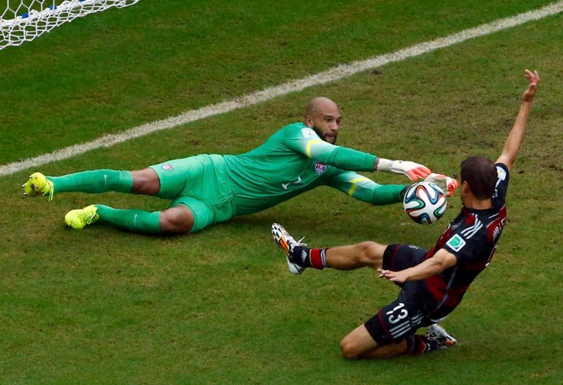 Germany's Thomas Mueller challenges goalkeeper Tim Howard of the U.S. during their 2014 World Cup Group G soccer match at the Pernambuco arena in Recife, Brazil on June 26, 2014.