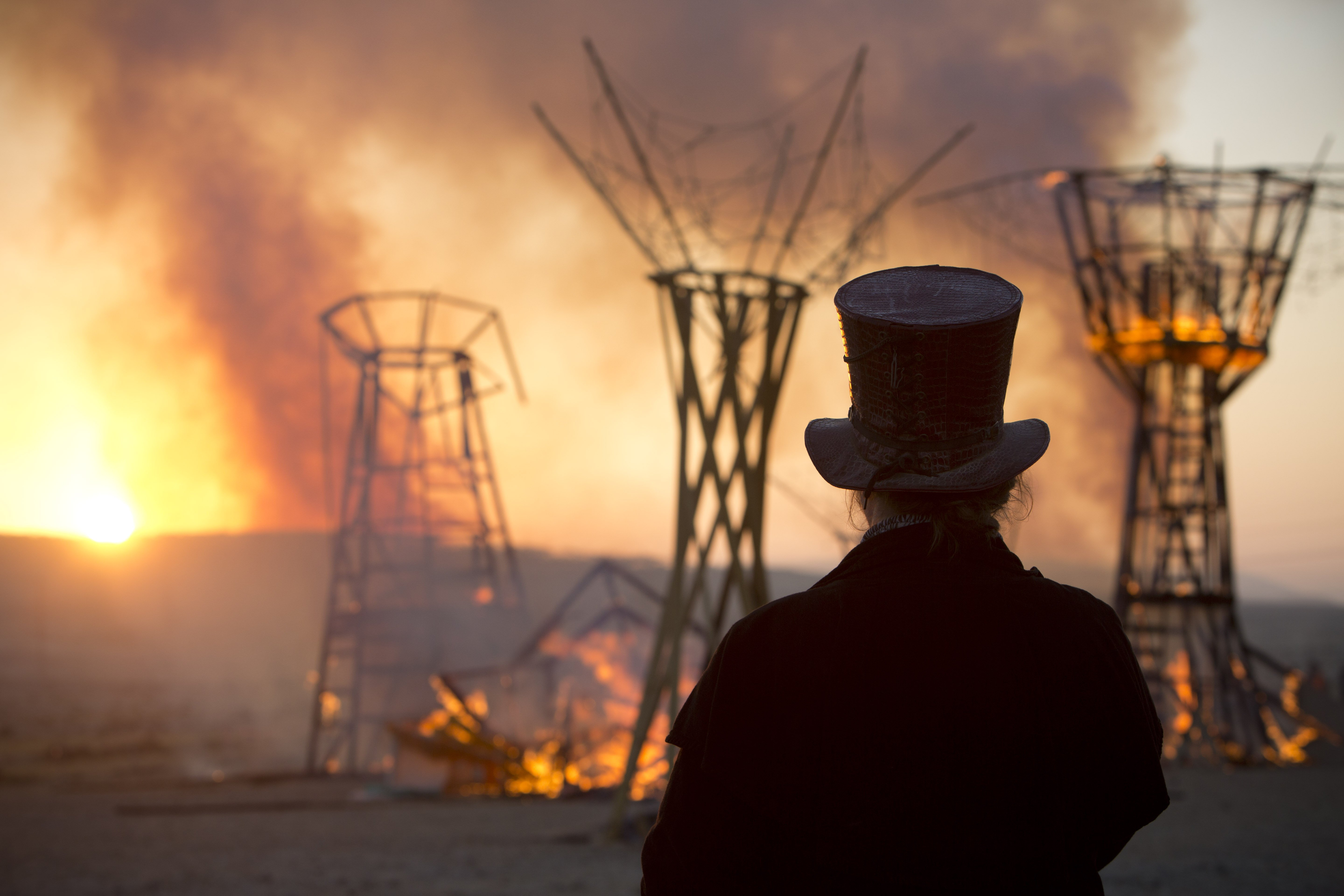 A man looks at a wooden sculpture that was set on fire at Israel''s first Midburn festival in the Negev Desert, Israel on June 7, 2014.