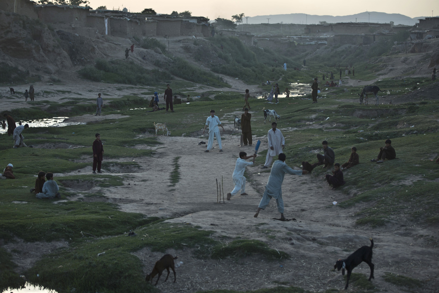 June 3, 2014. Internally Displaced Pakistanis from tribal areas and Afghan refugees play cricket, on the outskirts of Islamabad, Pakistan.