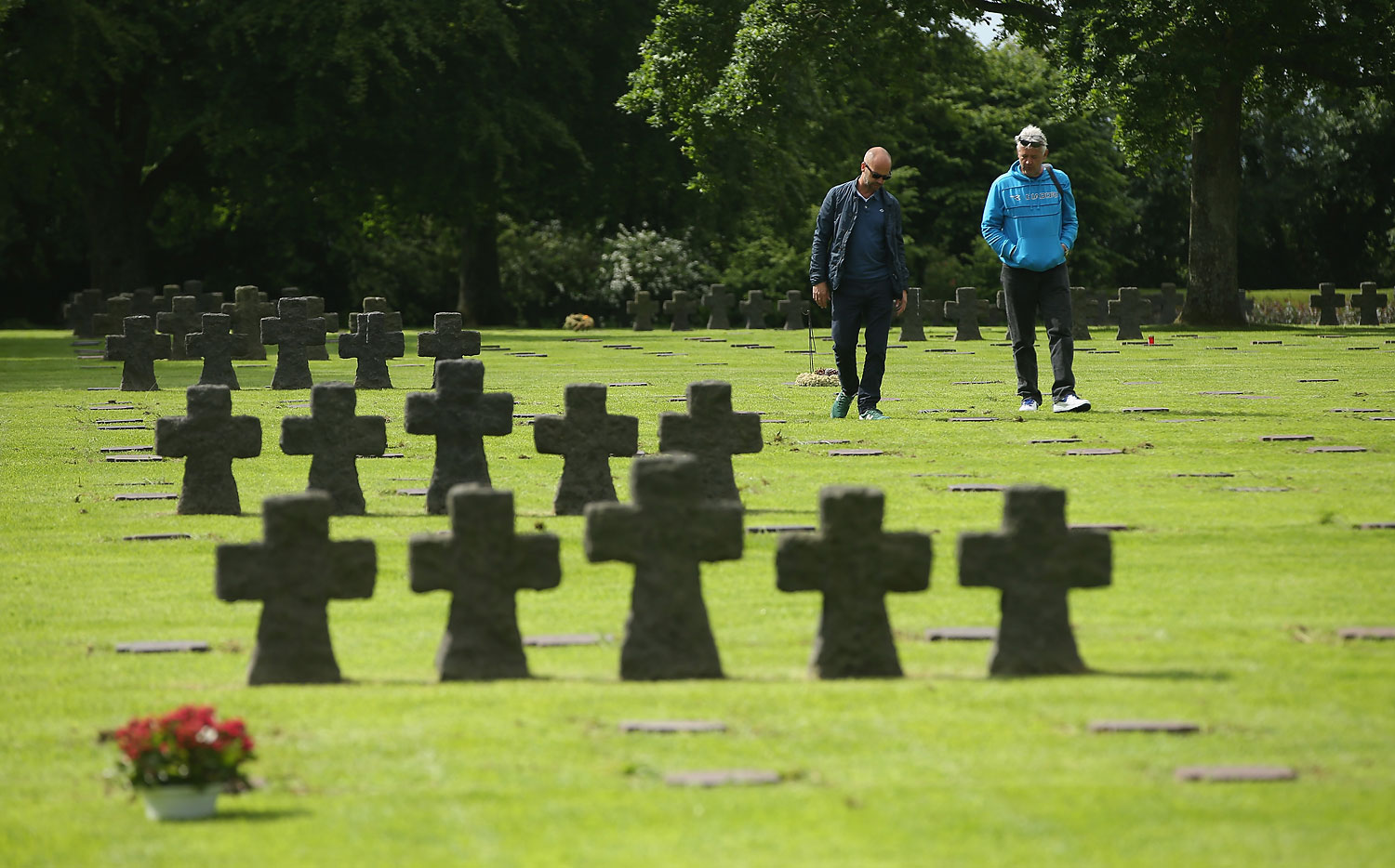 Visitors walk among gravestones at the German Cemetery where approximately 21,000 German World War II soldiers are buried on June 5, 2014 at La Cambe, France.