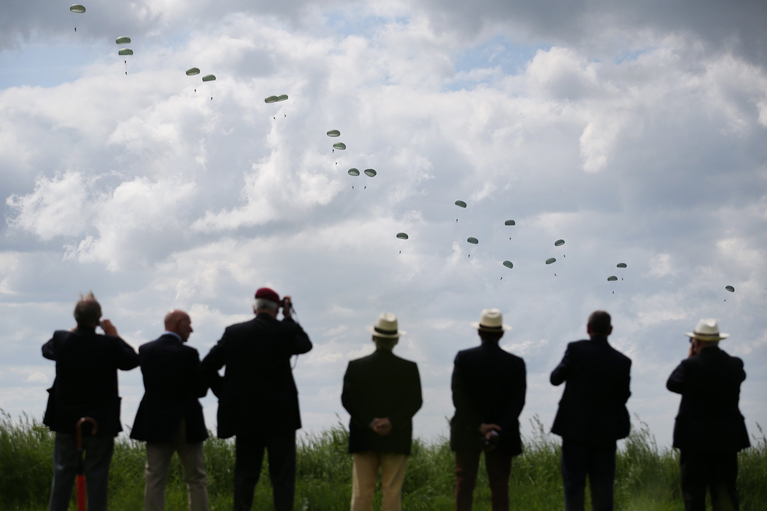 June 5, 2014. People watch as a parachute drop takes place on near Ranville, France. Friday 6th June is the 70th anniversary of the D-Day landings.